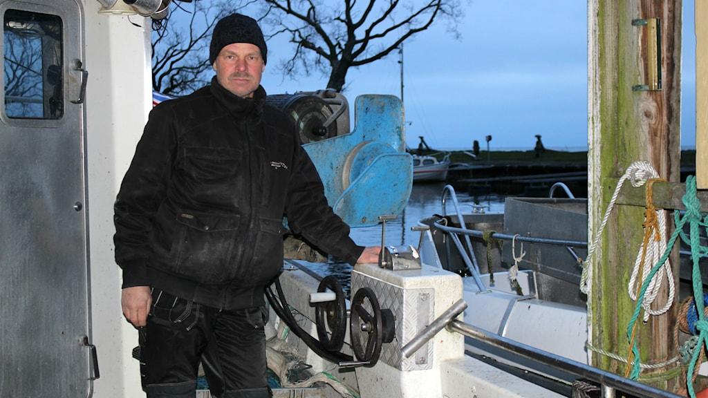 Fiskaren Rolf Gustavsson står i sin båt i båthuset i Hjo.