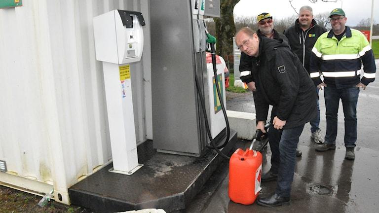Bengt Persson tankar på containermacken I Slutarp. Bakom honom står Peter Nordh, Patrik Haller och Håkan Pettersson från Falköpingsföretaget som satsar på småmackar.