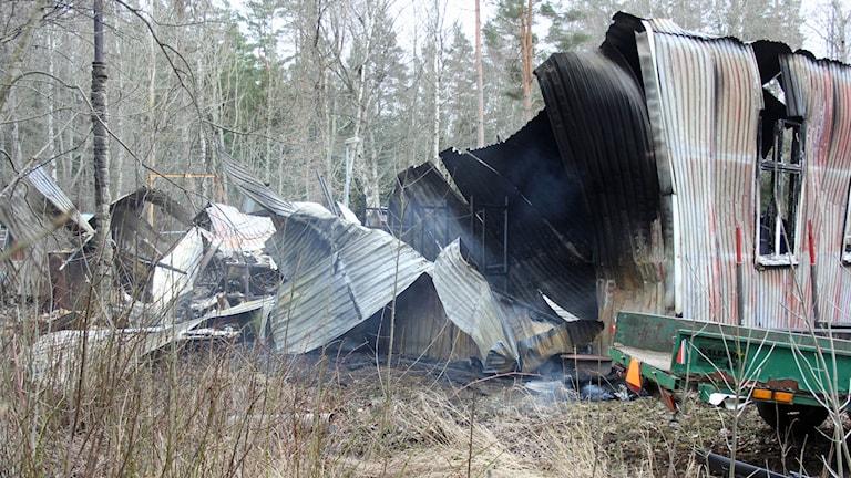 Brandrester av verkstad i plåt. Endast en del av en vägg står fortfarande upp. Foto: Ridder Karlsson /Skagerns Nyheter.