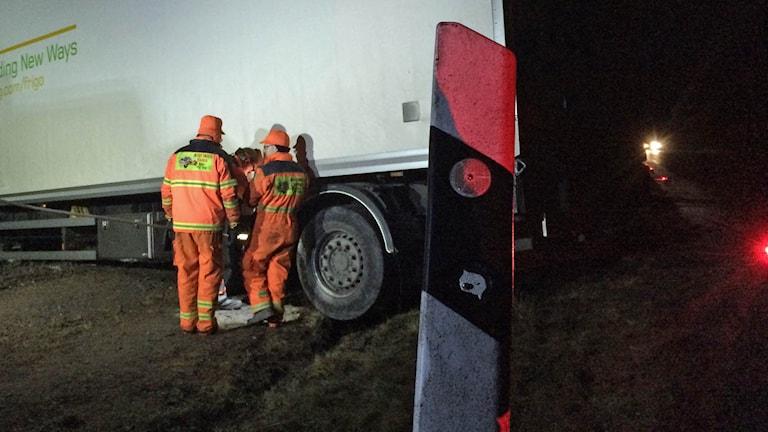 Bärgningspersonal inspekterar lastbilssläp. Foto: Mats Öfwerström / Sveriges Radio.