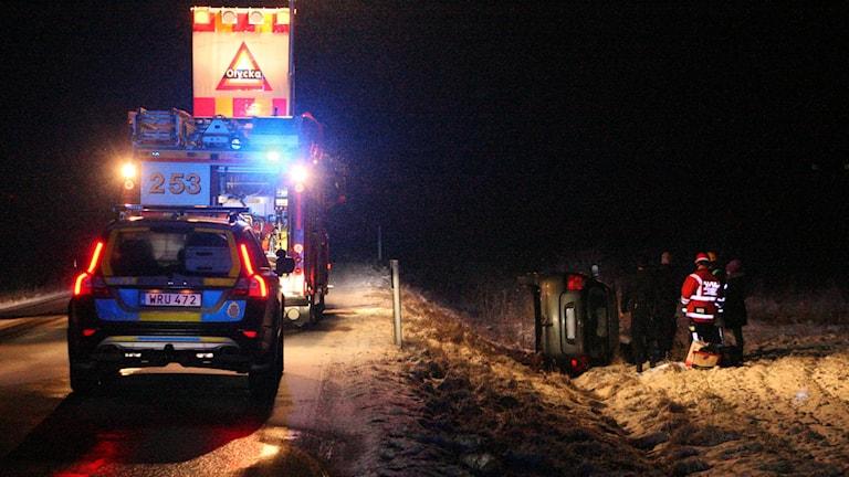 Polisbil och brandbil på vägen. Personbil liggande på sidan i diket, räddningspersonal. Foto: Torbjörn Axelsson.