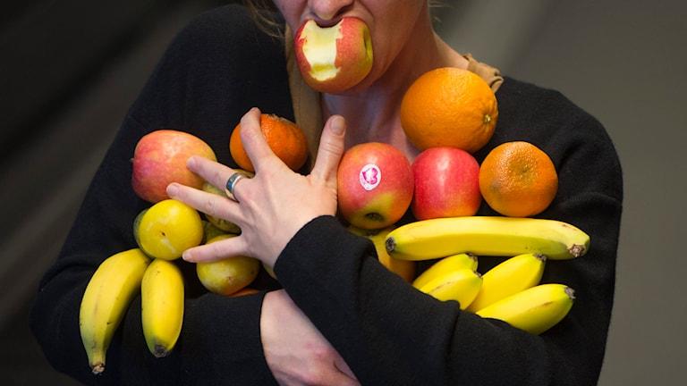 Person med frukt i famnen.