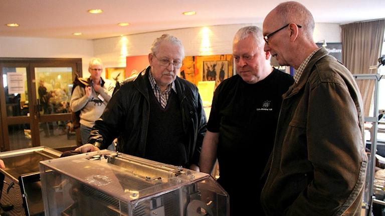 Jan Gustavsson i mitten visar en automatisk avtäckningsmaskin för Torsten Andersson från Skövde (till vänster) och Kjell Carlsson (till höger) från Skälvum. Foto: Hanna Ljungberg/P4 Skaraborg
