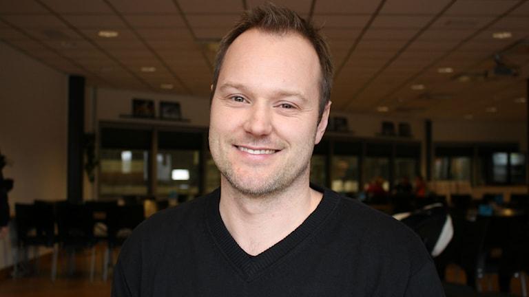 Magnus Muhrén tittar in i kameran och ler.