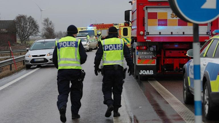 Två poliser går på vägen omgiven av räddningsfordon.