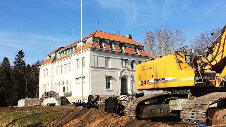 En grävskopa parkerad bredvid den gamla mangårdsbyggnaden på Aspö. Visst rivningsarbete påbörjat. Foto: Marthina Stäpel/P4 Skaraborg.