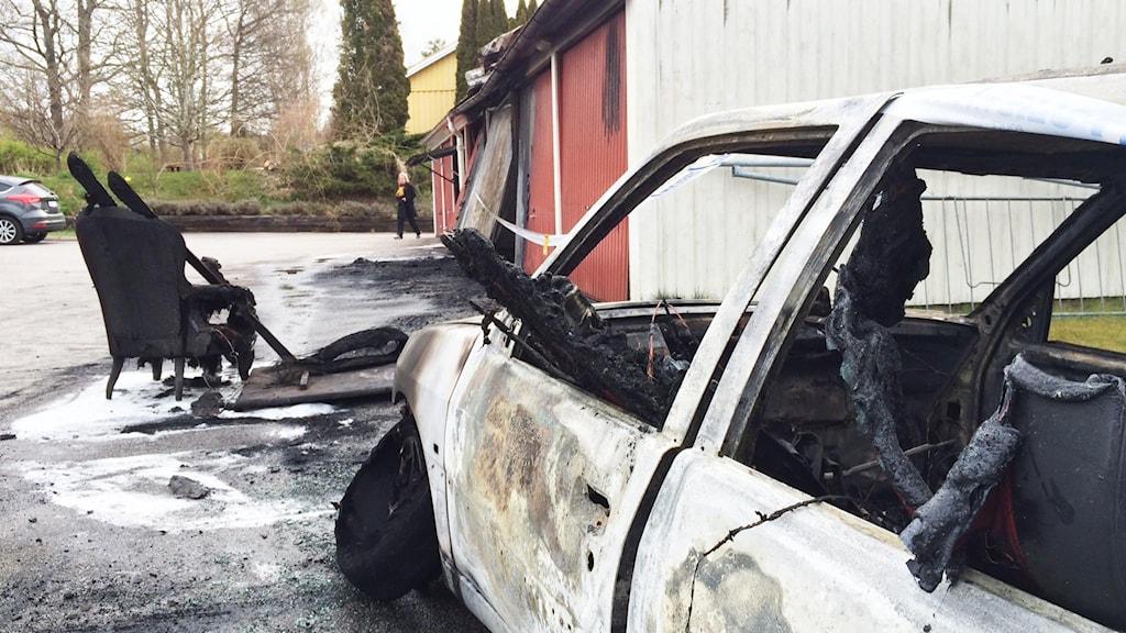 En utbränd bil och delvis brandförstörd garagelänga. Fåtölj som brunnit. Foto: Mats Öfwerström / Sveriges Radio.
