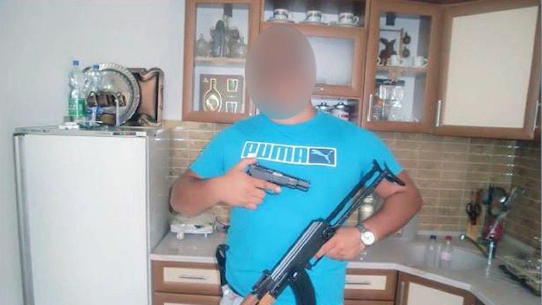 Man poserar med vapen. Bild från förundersökningen.