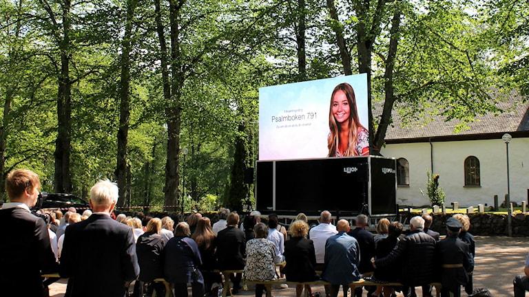 Åskådare följer Lisa Holms begravning utanför kyrkan. Foto: Hannah Zahr/Sveriges Radio