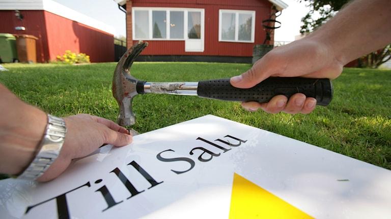 """Någon spikar fast en """"till salu""""-skylt framför ett rött hus."""