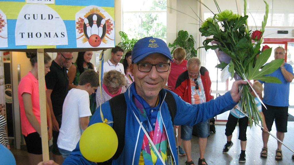 """Thomas Andersson på resecentrum i Skövde. Han har på sig en OS-keps och sina tre medaljer hänger runt halsen. I ena handen har han ett plakat där det står """"Guld-Thomas"""" och i den andra en bukett blommor. Foto: Tommy Alexandersson/Sveriges Radio"""