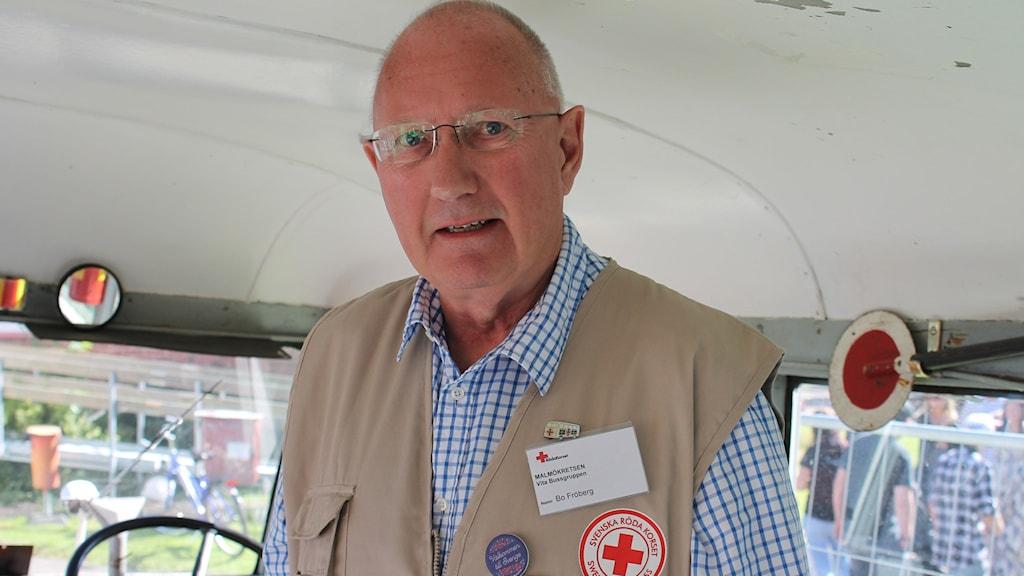 Bo Fröberg tittar in i kameran. Han står inne i den vita bussen och har på sig en beige väst med ett rött kors på.