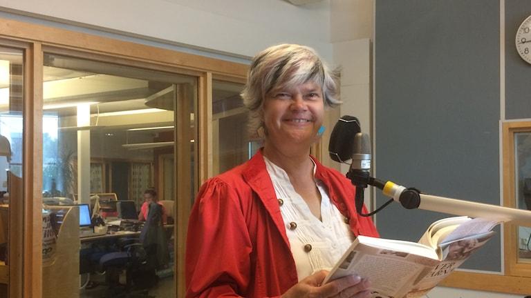 Yvonne Eriksen, P4 Skaraborgs läsinspiratör, i studion med en bok i handen. Foto: Margareta Lilja/Sveriges Radio