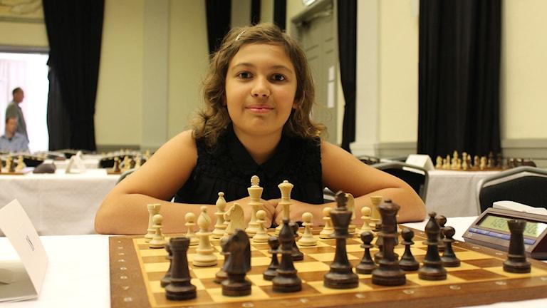 Tolvåriga schackspelaren Linnea Andersson från Lidköping sitter framför en spelbricka med schackpjäser uppställda på. Hon tittar in i kameran och ler. Hon har brunt, axellångt vågigt hår med ett hårspänne i luggen. Foto: Annelie Hüllert-Storm/Sveriges Radio