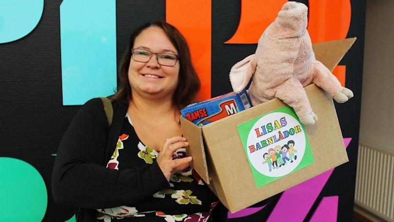 Lisa Wallenstein med leksaker i en låda.