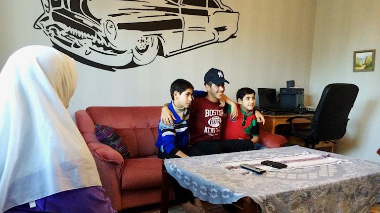 Kader Aweis håller om sina småbröder Ahmad och Mahmoud. Mamma Snaa till vänster. Foto: Mats Öfwerström / Sveriges Radio