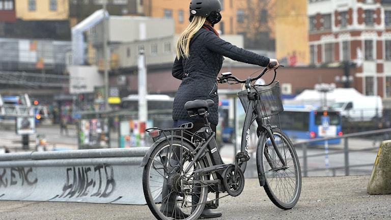 En kvinna står med ryggen vänd mot kameran bredvid en elcykel i Stockholms innerstad.