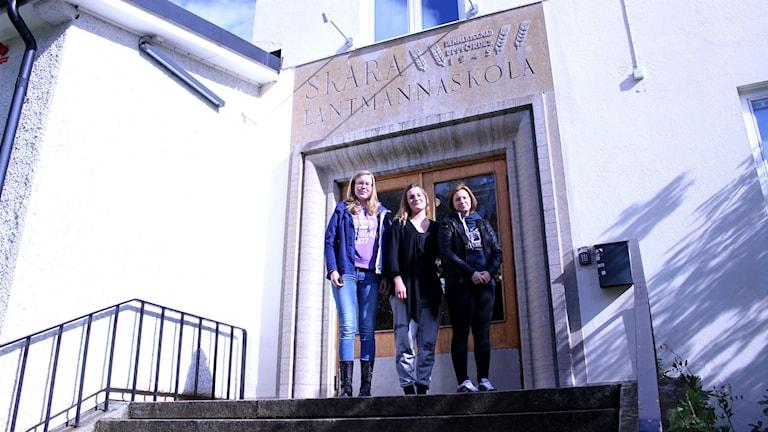 På bilden står tre elever på trappan upp till Uddetorp. Fotot är taget lite nedifrån.