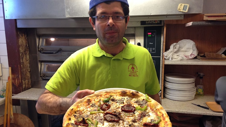 Remzi Öz presenterar den färdigbakade älgpizzan. Foto: Tommy Alexandersson/Sveriges radio