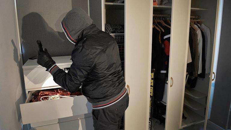En inbrottstjuv letar efter smycken och andra värdesaker under ett inbrott i en bostad. Foto: Anders Wiklund / TT.