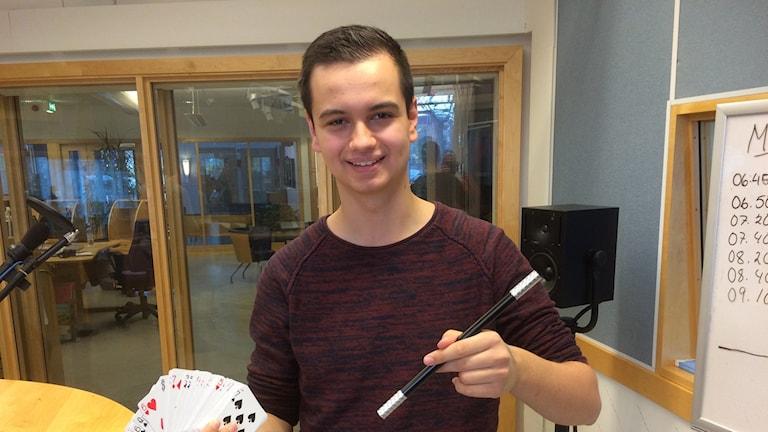 Adin Barlov står med sin trollstav och kortlek. Foto: Torbjörn Borg / Sveriges Radio