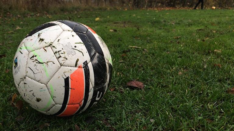 Bilden föreställer en fotboll som ligger nära kameran. I bakgrunden ser man en person som sparkar en boll. Foto: Annelie Hüllert-Storm/Sveriges Radio