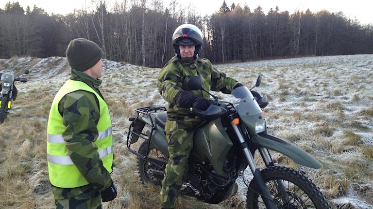 Freddie Nilsson sitter på en motorcykel och får instruktioner av Kapten Fredrik Holmgren. Foto: Linnéa Frimodig/ Svergies Radio