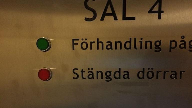 """Närbild på dörren in till rättsalen där det står """"sal 4"""". Under två knappar där det står """"förhandling pågår"""" och """"stängda dörrar""""."""