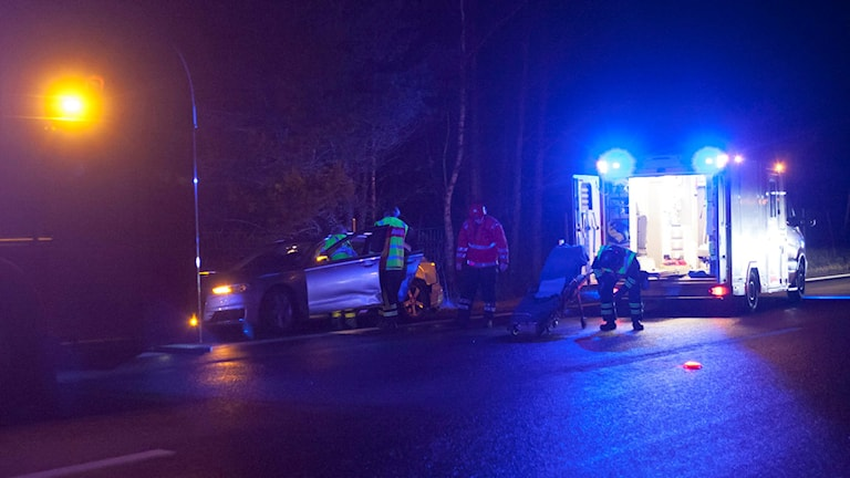 Ambulanspersonal har just öppnat förardörren till en inblandad personbil. En bår har lastats ur ambulansen. Foto: Torbjörn Axelsson.