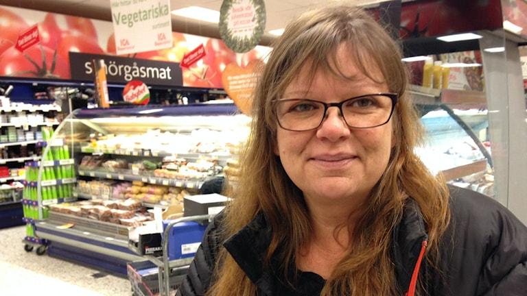 Kristina Hellund tittar in i kameran. Hon står i en livsmedelsbutik. Hon har glasögon och långt brunt hår. Foto: Annelie Hüllert-Storm/Sveriges Radio