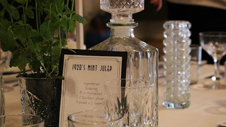 En bild av bordsdekorationen. Ett kort som det står Mint Julep på med ett recept på drinken Mint julep. Bredvid kortet står en mynta-växt. Foto: Annelie Hüllert-Storm/Sveriges Radio