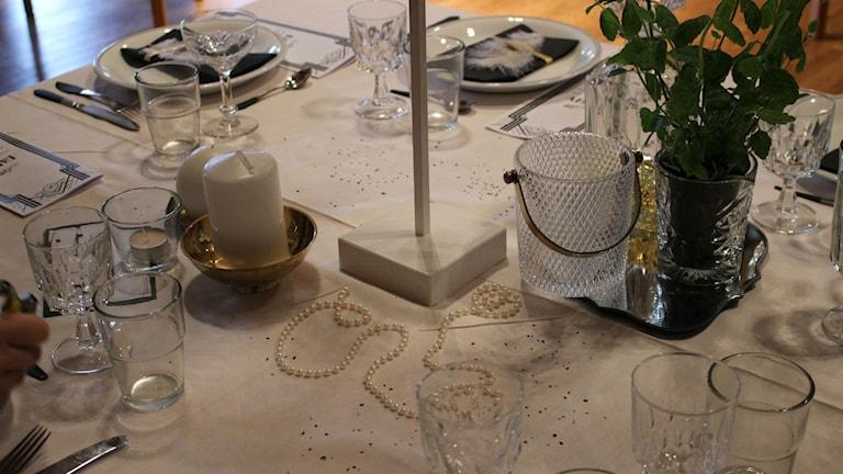 En bild lite ovanifrån nära bordets mittpunkt. Det ligger ett pärlhalsband som dekoration på duken. Foto: Annelie Hüllert-Storm/Sveriges Radio
