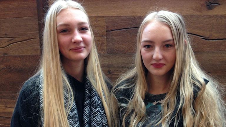 Hilda Falk och Elinor Falk tittar in i kameran. Båda har långt blont hår och står framför en trävägg. Foto: Annelie Hüllert-Storm/Sveriges Radio