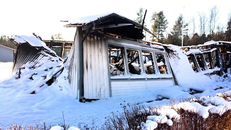 Snötäckta brandrester där ytterväggarna är på väg att rasa in. Foto: Marthina Stäpel / Sveriges Radio.