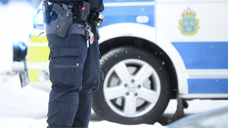 Polis framför en polisbil. Foto: Fredrik Sandberg/TT
