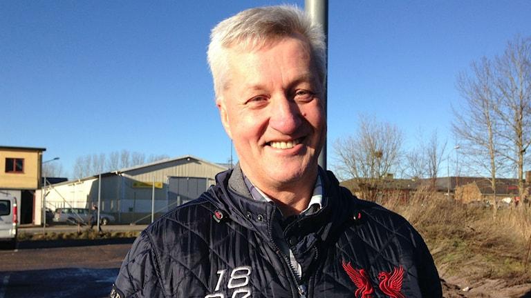 Lars Lundberg står med solen i ansiktet och ler in i kameran. Han har på sig en mörkblå jacka och har grått kort hår. Foto: Annelie Hüllert-Storm/Sveriges radio