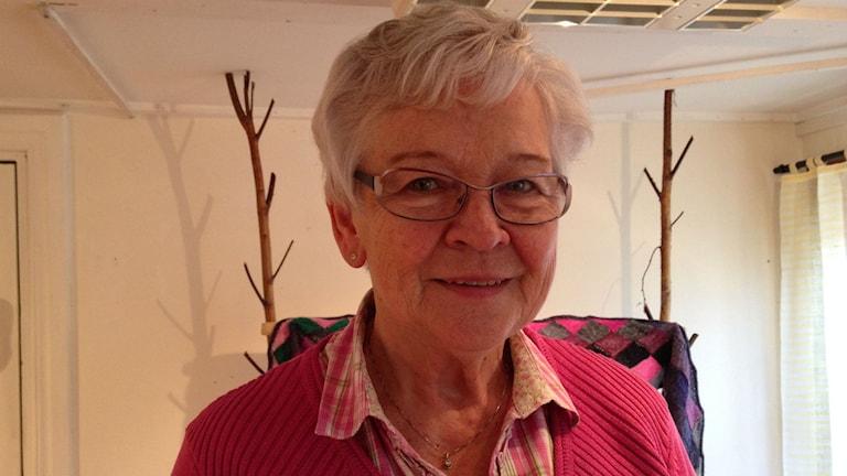 Birgitta Carlsson tittar in i kameran och ler. Hon har kort grått hår och glasögon. En rosa tröja och en rosa-rutigskjorta under tröjan. Foto: Annelie Hüllert-Storm/Sveriges Radio