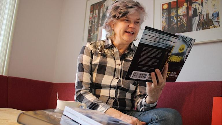 Yvonne Eriksen sitter och läser en bok.