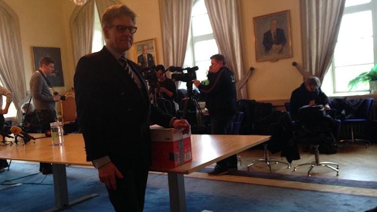 Bertil står med en papplåda där pappren med domen ligger i.