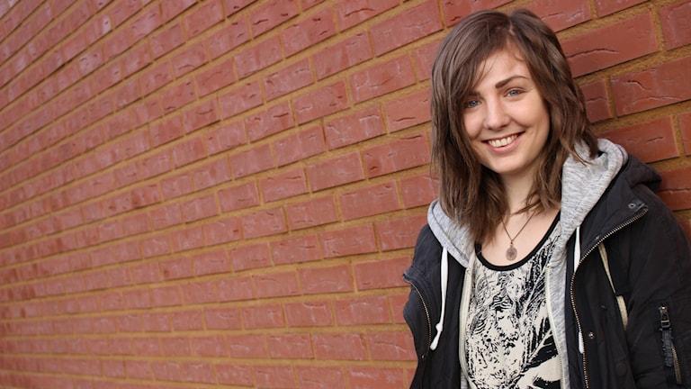 Emina står lutad mot en tegelvägg. Hon har luvtröja på sig och hon ler.