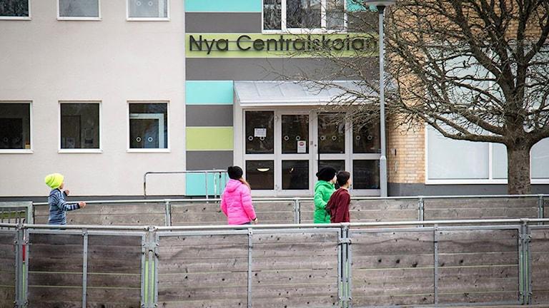 Skolgård med några barn och entré till Nya Centralskolan i Grästorp.