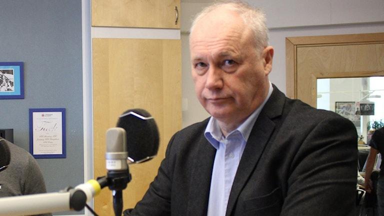 En äldre man med tunt vitt hår i skjorta och kostym står i radiostudion.