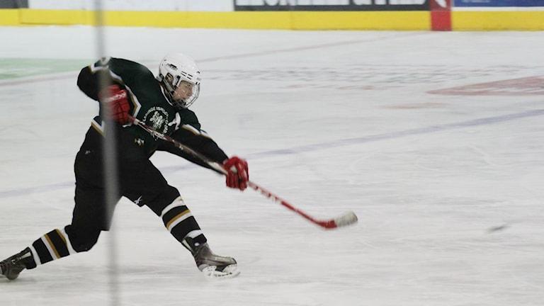 Lina Ljungblom från Skövde mitt på isen med klubba i hand. Hon skjuter mot mål.