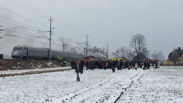 Resenärer har evakuerats och står på en åker utanför det brinnande tåget.