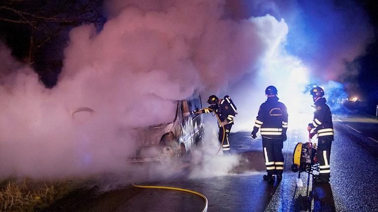 Brandman står nära bilen och sprutar med slang in genom fönster. Mycket rök och ånga.
