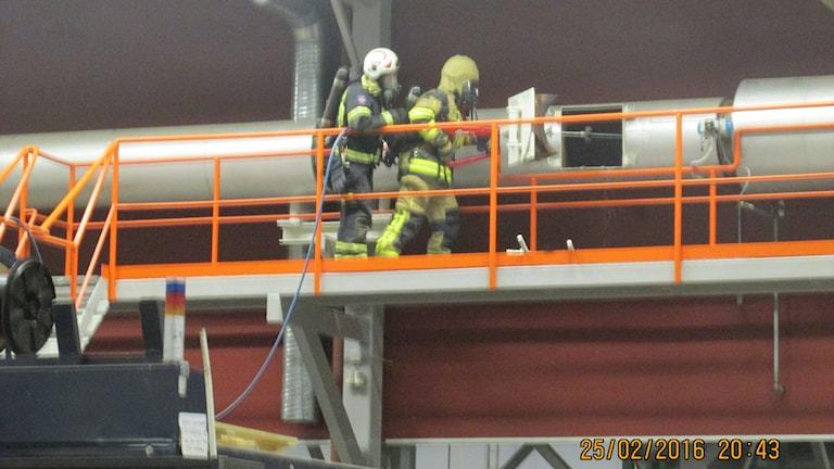 Brandmän släcker i en trumma inne i fabriken.