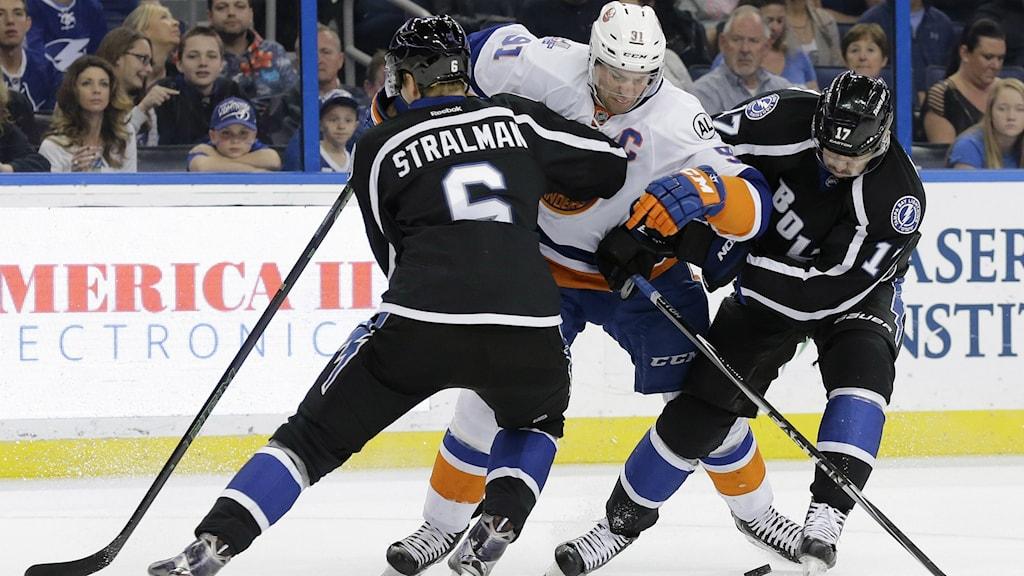 Hockeyspelaren Anton Strålman försöker stoppa en annan spelare.