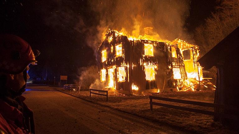 Tvåvåningshus. Hela byggnaden brinner kraftigt.