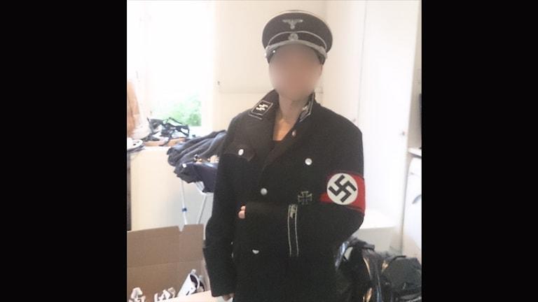 Kvinnliga föreståndaren på stödboendet poserar i nazistuniform