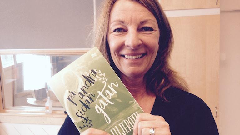 Anne Liljeroth håller upp sin bok med titeln På andra sidan gatan.